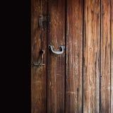 Vecchia porta di legno stagionata aperta con la maniglia lucidata del metallo, il fermo d'acciaio ed il bullone di legno appenden Fotografie Stock Libere da Diritti