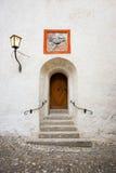 Vecchia porta di legno stagionata marrone in costruzione di pietra bianca Fotografie Stock Libere da Diritti