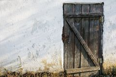 Vecchia porta di legno in una vecchia parete di pietra fotografia stock