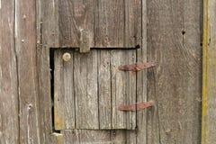 Vecchia porta in legno del granaio con le cerniere e la manopola Fotografia Stock
