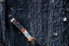 Vecchia porta nera con la maniglia arrugginita fondo, annata immagine stock