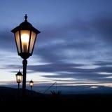 Vecchia posta della lampada in cielo di tramonto immagini stock