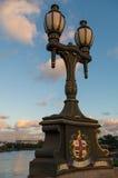 Vecchia posta della lampada sul ponte con lo stadio nel fondo Fotografia Stock
