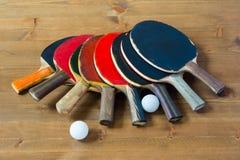 Vecchia racchetta che si trova un mucchio su una tavola e su due palle Fotografie Stock