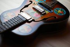 Vecchia retro chitarra con le immagini dei fiori fotografia stock libera da diritti