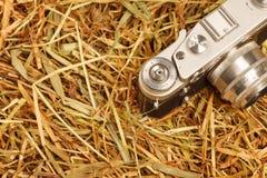 Vecchia retro macchina fotografica del film sul fondo del fieno Immagini Stock