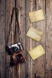 Vecchia retro macchina fotografica e strutture istantanee in bianco della foto su fondo di legno d'annata Fotografie Stock