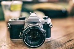 Vecchia retro macchina fotografica sul fondo astratto d'annata dei bordi di legno Effetto del grano del film immagine stock libera da diritti