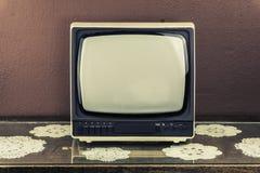 Vecchia retro TV sulla tavola d'annata, fondo marrone Immagine Stock Libera da Diritti
