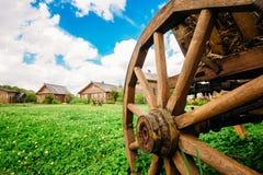 Vecchia ruota di vagone sui precedenti del villaggio con le capanne Fotografie Stock Libere da Diritti
