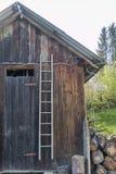 Vecchia scala del banco di legno contro la parete Fotografie Stock