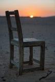 Vecchia, sedia alla moda e di legno sulla spiaggia con il tramonto Fotografia Stock Libera da Diritti