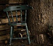Vecchia sedia blu-di legno in un angolo calmo, sotto un pino fotografia stock
