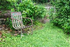 Vecchia sedia del metallo, copertura al suolo verde, spazio della copia, concetto di assenza di dolore di morte fotografie stock libere da diritti