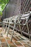 Vecchia sedia del metallo sul pavimento del mattone Fotografia Stock