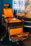 Vecchia sedia di barbiere in una stanza fotografia stock