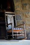 Vecchia sedia di oscillazione di Adirondack contro la parete di pietra Immagine Stock