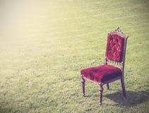 Vecchia sedia rossa antica d'annata su erba verde, backgroun astratto immagini stock