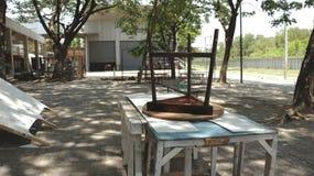 Vecchia sedia a tre gambe di legno delle feci che si trova sottosopra sulle Tabelle dipinte sbucciatura - Junkyard/abbandonato su immagini stock libere da diritti