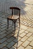 Vecchia sedia viennese sui ciottoli nel tramonto immagini stock libere da diritti