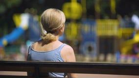 Vecchia seduta femminile triste sul banco del campo da giuoco ed esaminare i bambini, sterilità video d archivio