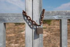 Vecchia serratura arrugginita del metallo che appende su una catena arrugginita del metallo Porte chiuse del metallo immagine stock libera da diritti