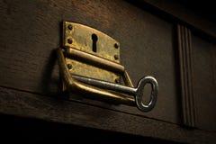 Vecchia serratura arrugginita in un cassetto di legno con una chiave Fotografie Stock