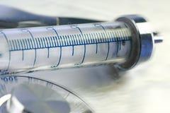Vecchia siringa di vetro sul primo piano brillante della superficie dell'acciaio fotografia stock