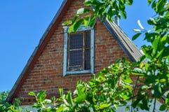 Vecchia soffitta verde sul tetto Il tetto di vecchia casa contro il cielo blu Fotografie Stock