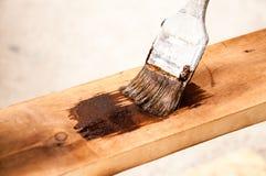 Vecchia spazzola in pittura marrone Dipinge un bordo di legno immagini stock libere da diritti