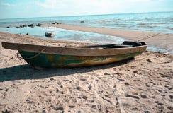 Vecchia spiaggia e la barca sulla sabbia Immagini Stock