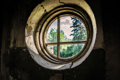 Vecchia stanza rovinata con la finestra rotonda Fotografie Stock