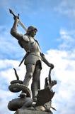 Vecchia statua che descrive il drago di uccisione dell'uomo Fotografie Stock Libere da Diritti