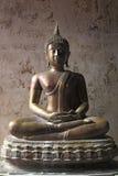 Vecchia statua del Buddha del metallo sul vecchio muro di cemento Fotografia Stock