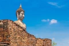Vecchia statua di Buddha che sta alta dietro la parete rovinata del tempio in ayu Fotografia Stock Libera da Diritti
