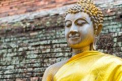 Vecchia statua di Buddha con il fondo del muro di mattoni Immagine Stock