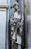 Donna di pietra anziana della statua con i fiori su un cimitero. fotografia stock libera da diritti