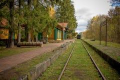 Vecchia stazione ferroviaria d'annata con il treno in Polonia, Bialowieza, fotografia stock libera da diritti