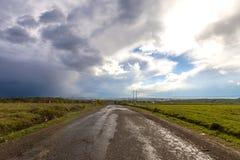 Vecchia strada incrinata dopo pioggia Cattiva via irregolare con i fori e lo sto Fotografie Stock Libere da Diritti