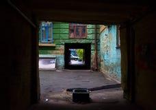 Vecchia strada transitabile scura con i graffiti Fotografia Stock