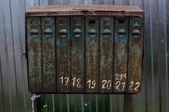 Vecchia struttura arrugginita della cassetta delle lettere con i numeri contro lo sfondo del recintare la campagna Fotografie Stock