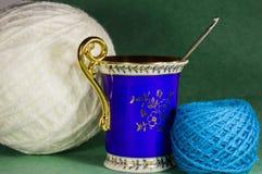 Vecchia tazza, gancio per tricottare e palle bianche e blu di filato Fotografie Stock