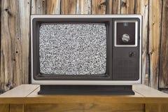 Vecchia televisione con lo schermo statico e la parete di legno rustica immagine stock