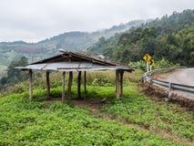 Vecchia tettoia di legno vicino alla strada asfaltata della curva Fotografie Stock