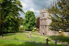 Vecchia torre di chiesa sul prato di campanule fotografia stock