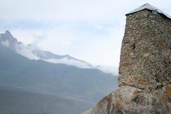 Vecchia torre di pietra nelle montagne nebbiose Fotografia Stock