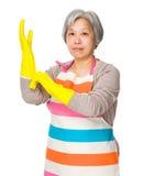 Vecchia usura della casalinga con i guanti di plastica immagini stock libere da diritti
