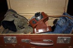 Vecchia valigia con gli stivali, la macchina fotografica, i jeans e i sunglass Immagini Stock Libere da Diritti