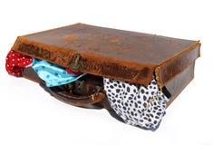 Vecchia valigia di cuoio marrone avariata con la biancheria intima Fotografia Stock Libera da Diritti