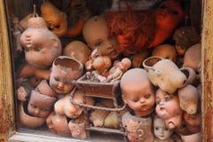 Vecchia vetrina con molte vecchie bambole delle teste fotografia stock